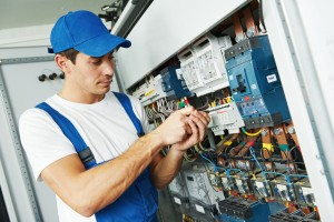 Young adult electrician builder engineer screwing equipment in f